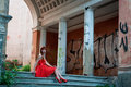 The girl in the red dress walking through ruins Royalty Free Stock Images