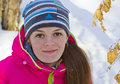 The girl in the red jacket looking up directly into the camera lens closeup squatting amid snow Stock Image