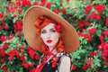 Girl with red lips in rose print dress on summer garden. Spring blossom flower. Redhead model in summer hat on valentines Royalty Free Stock Photo