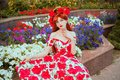 Girl with red lips in stylish flower dress with rose print on flowerbed background. Redhead model with red nails and rose flower Royalty Free Stock Photo