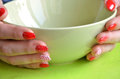 Girl with red nails with dots on her fingers hold green bowl, closeup Royalty Free Stock Photo