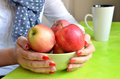 Girl with red nails on her fingers hold green bowl full of apples Royalty Free Stock Photo