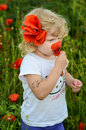 Girl with red poppy blond chield in a field Stock Images