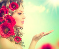 Girl with red poppy flowers hairstyle beauty and open hands Royalty Free Stock Photography