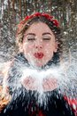 stock image of  The girl in the red rim blows the snow from the palm