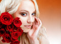 Girl with red roses in her blond hair. Stock Image
