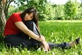 Girl in red shirt siting near tree Stock Photo