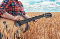 Girl in the red shirt in wheat field plays the acoustic guitar. Beautiful nature at bright sunny summer day. Royalty Free Stock Photo