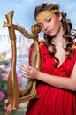 Girl in a red tunic against greece cute with harp on background of Royalty Free Stock Photography