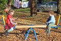 Girl in red vest and her brother on seesaw