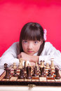 Girl relaxes during chess a young looks up over the chessboard at the camera Royalty Free Stock Image