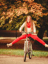 Girl relaxing in autumnal park with bicycle. Royalty Free Stock Photo