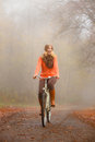 Girl relaxing in autumnal park with bicycle Royalty Free Stock Photo