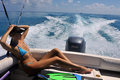 Girl relaxing on the back of motor boat cruising speed at tropical water Royalty Free Stock Image