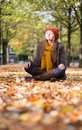 Girl relaxing and meditating in park on a fall day Stock Photography