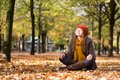 Girl relaxing and meditating in park on a fall day Stock Photos