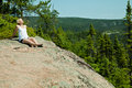 Girl relaxing on a rock in the middle of the nature Stock Photography