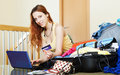 Girl reserving hotel online with laptop and credit card at home Stock Photos