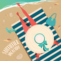 Girl resting on the beach top view of a in wide brimmed hat sitting a striped mat by sea summer vacation concept Royalty Free Stock Photos