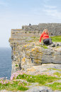 Girl resting in dun aengus an ancient fort cliffs aran islands republic of ireland Royalty Free Stock Photo