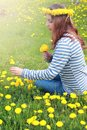 Girl resting on a sunny day in meadow of yellow dandelions