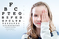 Girl reviewing eyesight close up portrait of eye sight closing eye with hand test chart in background Royalty Free Stock Photography