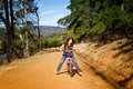 Girl riding bike a young her on a forest road Royalty Free Stock Image