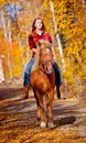 Girl riding horse in the fall time Royalty Free Stock Image