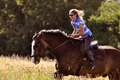 Girl riding horse in meadow Royalty Free Stock Photo