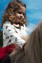 Girl riding mini horse with blue sky Stock Photo