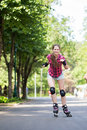 Girl riding rollerblades beautiful rides her in park Royalty Free Stock Photography