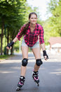 Girl riding rollerblades beautiful rides her in park Stock Photos