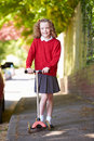 Girl riding scooter on her way to school smiling at camera Royalty Free Stock Images