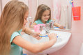 Girl rinse the toothbrush under running tap water Royalty Free Stock Photo