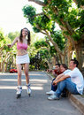 The girl on rollers under exulting of guys Royalty Free Stock Photography