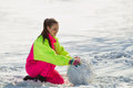 Girl rolling a huge snowbal smiling snowball in wintertime Stock Photography