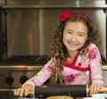 Girl rolling out holiday cookies a pretty with long brown curly hair smiles and has fun while cookie dough to bake for the Stock Photography