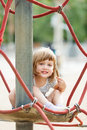 Girl on ropes at playground area in summer Royalty Free Stock Photo