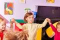 Girl roundelay with children in kindergarten Royalty Free Stock Photo