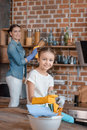 Girl in rubber gloves with cleaning supplies and mother behind in kitchen