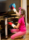 Girl in rubber gloves cleaning TV screen from dust with cloth Royalty Free Stock Photo