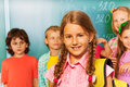 Girl with rucksack on shoulders near blackboard yellow her the and other pupils behind her Royalty Free Stock Image