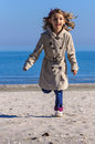 Girl running on beach beautiful child in fall clothes front view Stock Image