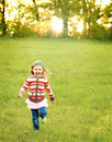 Girl running in green field at sunset Royalty Free Stock Photo