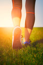 Girl running shoes closeup green grass woman fitness runner athlete at seaside healthy lifestyle Royalty Free Stock Photos