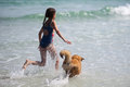 Girl runs with a dog through the water Royalty Free Stock Image