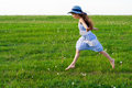 Girl runs on meadow with dandelions in hat green Stock Photos