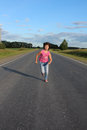 The girl runs on road asphalted it jeans and a pink t short are dressed hair of flutter a wind Royalty Free Stock Images