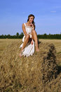 Girl in a rural clothing sitting on the haystack Stock Image