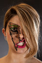 Girl s face in lightning makeup covered by hair lip snarl Stock Photos